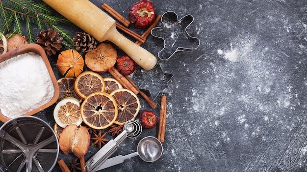 Ингредиенты для приготовления рождественской выпечки: мука, кухонная утварь и сухофрукты на темном фоне, вид сверху