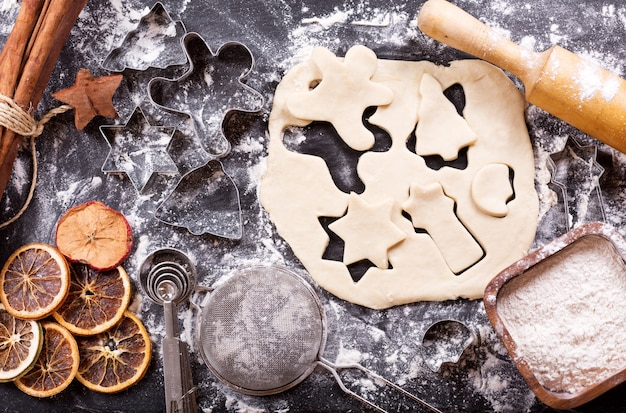 Ингредиенты для приготовления рождественских пряников: тесто для пряников, формы для выпечки и кухонная утварь на темном столе, вид сверху