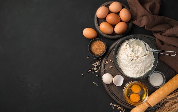 小麦粉料理の材料。黒の背景に小麦粉、卵、砂糖。上面図、コピースペース。