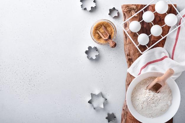 Ингредиенты для приготовления домашней выпечки. фон выпечки с мукой, яйцами, кухонными принадлежностями, посудой и формами для печенья на белом мраморном столе. вид сверху. плоский стиль. макет.