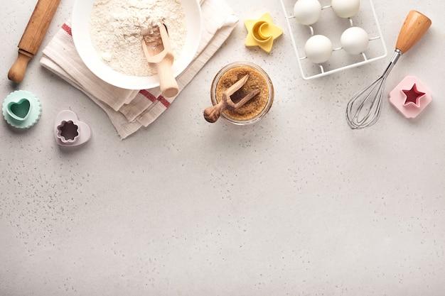 수제 베이킹 요리 재료. 흰색 대리석 테이블에 밀가루, 계란, 주방 도구, 기구, 쿠키 금형으로 배경을 굽습니다. 평면도. 플랫 레이 스타일. 조롱.