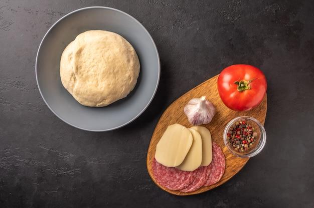 Ингредиенты для приготовления домашней пиццы с моцареллой и салями на темном фоне.