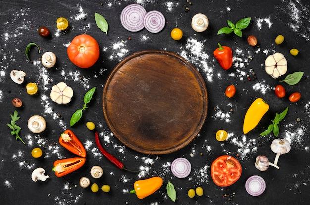 검은 석재 배경 상단 보기에 빈티지 커팅 보드와 함께 이탈리아 수제 피자를 요리하기 위한 재료