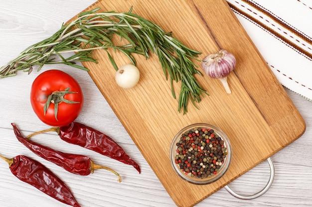 肉や魚を調理するための材料。にんにく、ガラスのボウルにピーマン、唐辛子、トマト、タマネギ、ローズマリーを木製のまな板に。上面図。