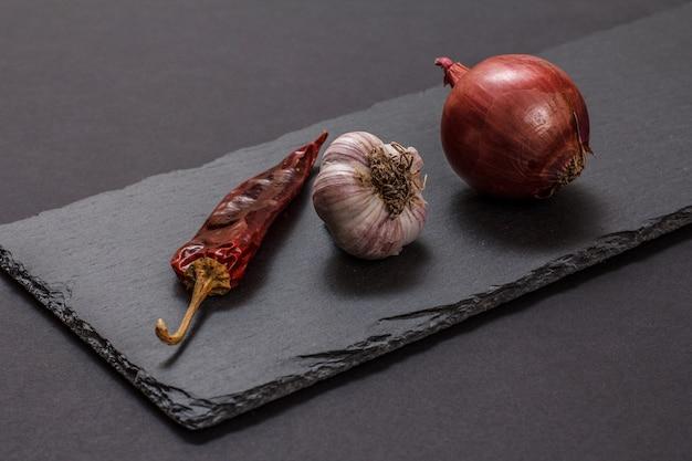 고기나 생선 요리 재료. 마늘, 마른 칠리 페퍼, 양파는 돌 커팅 보드와 검은색 배경에 있습니다.