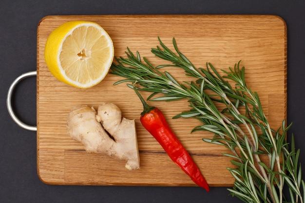 肉や魚を調理するための材料。木製のまな板にショウガの根、唐辛子、レモン、ローズマリー。上面図。