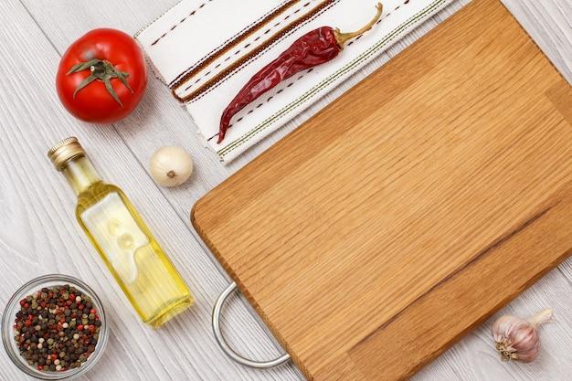 肉や魚を調理するための材料。オールスパイスペッパー、オイルのボトル、ニンニク、唐辛子、トマト、木製のまな板が入ったガラスのボウル。上面図。
