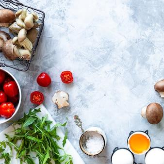 灰色のコンクリート背景で調理するための材料。新鮮なグリーンアスパラガス、卵、ベーコン、マッシュルーム、トマト、ルッコラの束。上面図。コピースペース