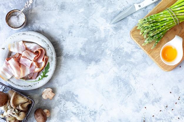 灰色のコンクリート背景で調理するための材料。新鮮なグリーンアスパラガス、卵、ベーコン、キノコの束。上面図。コピースペース