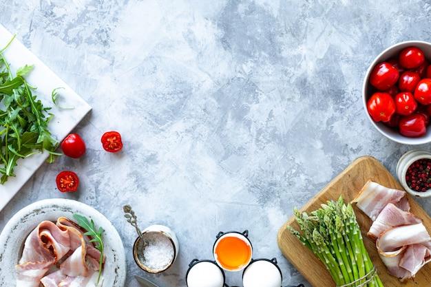 灰色のコンクリート背景で調理するための材料。新鮮なグリーンアスパラガス、卵、ベーコン、トマト、ルッコラの束。上面図。コピースペース