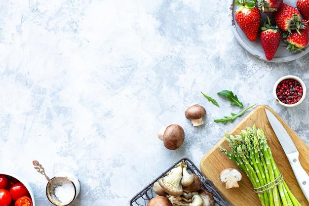 灰色のコンクリート背景で調理するための材料。新鮮なグリーンアスパラガス、マッシュルーム、イチゴ、トマト、ルッコラの束。上面図。コピースペース