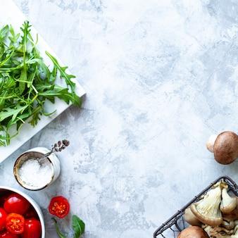 灰色のコンクリート背景で調理するための材料。新鮮なグリーンアスパラガス、マッシュルーム、トマト、ルッコラの束。上面図。コピースペース
