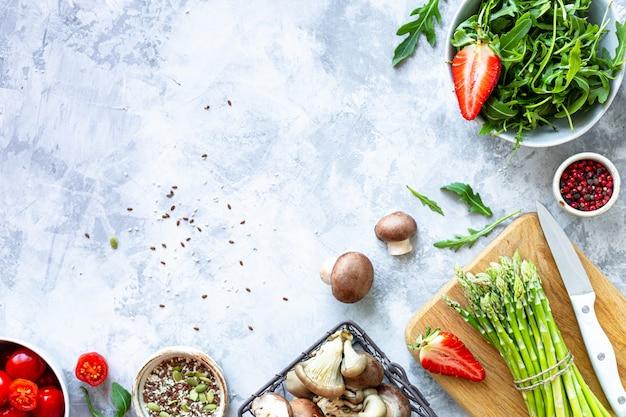 灰色のコンクリート背景で調理するための材料。新鮮なグリーンアスパラガス、イチゴ、マッシュルーム、トマト、ルッコラの束。上面図。コピースペース