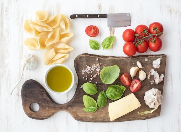 パスタを調理するための材料。コンキリオーニ、バジルの葉、チェリートマト、パルメザンチーズ、オリーブオイル、塩、白い木製の上の素朴なクルミのまな板にニンニク