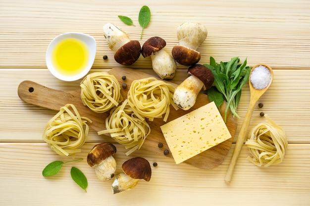 パスタを調理するための材料。軽い木製の背景にポルチーニ茸、チーズ、セージのフェットチーネを残します。