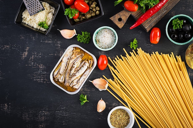 Ингредиенты для приготовления макаронных спагетти alla puttanesca - итальянского блюда из макарон с помидорами, маслинами, каперсами, анчоусами и петрушкой. вид сверху, плоская планировка