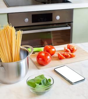 부엌 테이블과 스마트 폰에 토마토와 시금치 파스타 요리 재료.