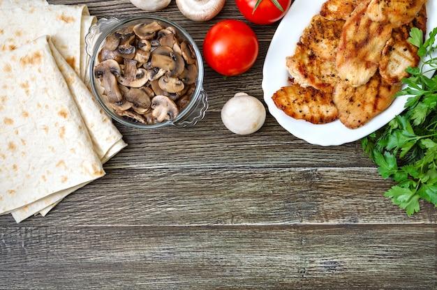 木製の背景の上面図でシャワルマやタコスを調理するための材料