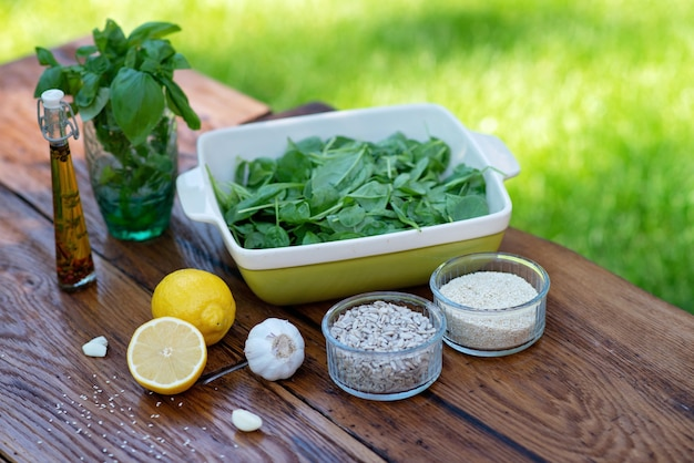 緑のほうれん草ソースにバジル、ニンニク、レモン、ヒマワリの種、オリーブオイル、ゴマを加えたスナックを調理するための材料。有機健康食品スナックまたは前菜。