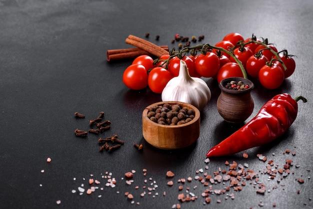 黒の背景に料理、スパイス、ニンニク、トマト、ハーブの材料