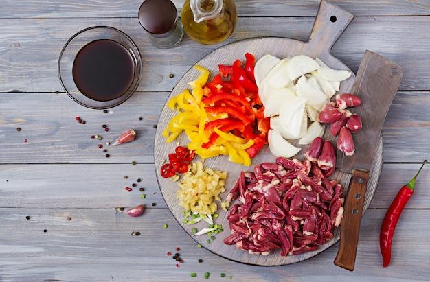 Ингредиенты для приготовления жаркого из куриных сердечек, паприки и лука. китайская кухня. вид сверху