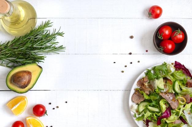 コピースペースで調理するための材料。白い木製のテーブルに新鮮なサラダ、ローズマリー、レモン、スパイス、オイルのボウル。食品の背景。健康的な食事の概念。