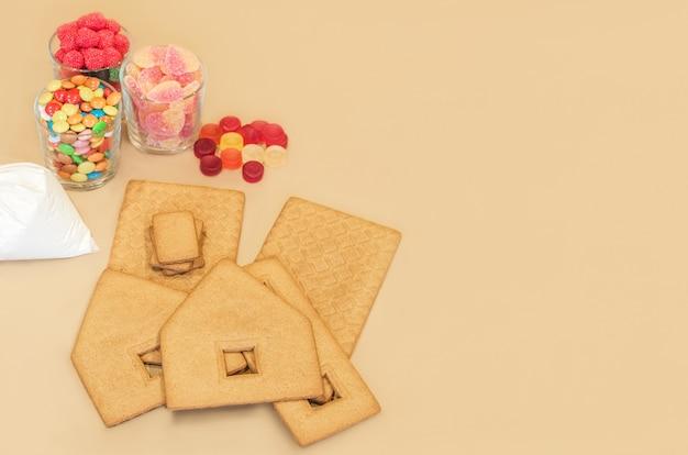 クラフト紙の背景にクリスマスジンジャーブレッドハウスを飾るための成分。クッキービスケット、アイシングバッグのフロスティングトッピング、キャンディーのセット。クリスマスジンジャーブレッドハウス作り。スペースをコピーします。
