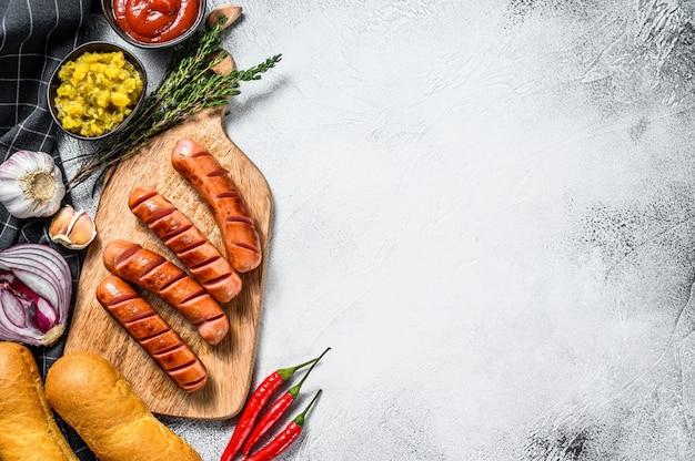 Ингредиенты для различных домашних хот-догов с жареным луком, чили, помидорами, кетчупом, огурцами и колбасой. вид сверху. копировать пространство