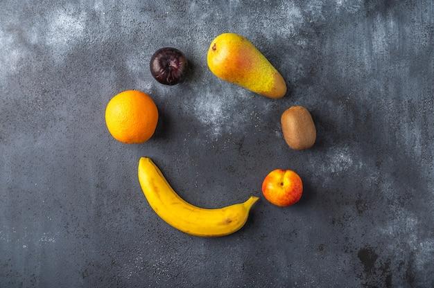Ингредиенты для фруктового салата лежат в форме круга на темной деревянной поверхности.