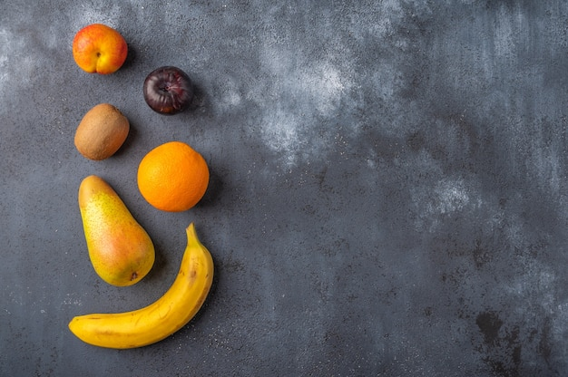 Ингредиенты для фруктового салата на темной деревянной поверхности