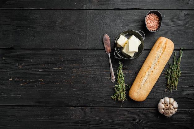 Ингредиенты для хлеба с чесноком и гербами, набор багетов, на черном фоне деревянного стола, плоская планировка, вид сверху, с копией пространства для текста