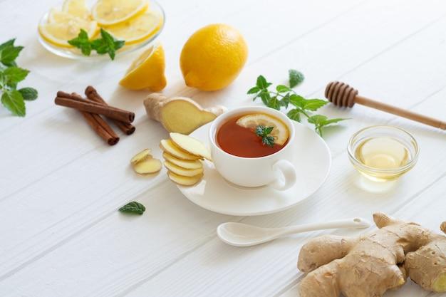 レモン、ハチミツ、ミント、シナモンと白いテーブルの上のジンジャーティーの材料