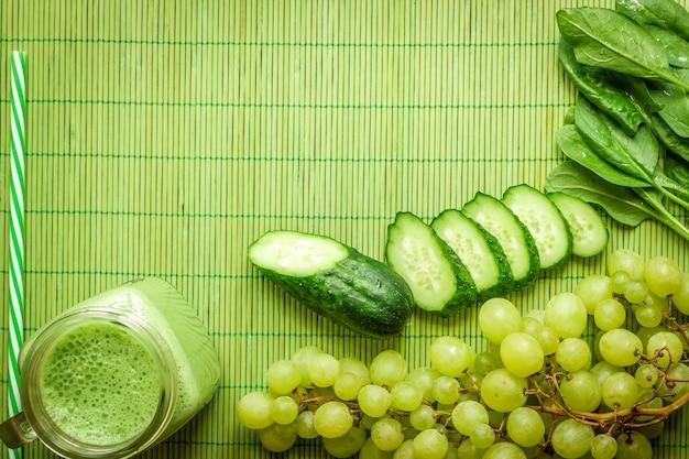녹색 해독 스무디의 재료입니다. 녹색 배경에 시금치, 포도, 오이. 텍스트를 위한 장소가 있는 평평한 위치. 완전 채식 및 건강 식품 개념