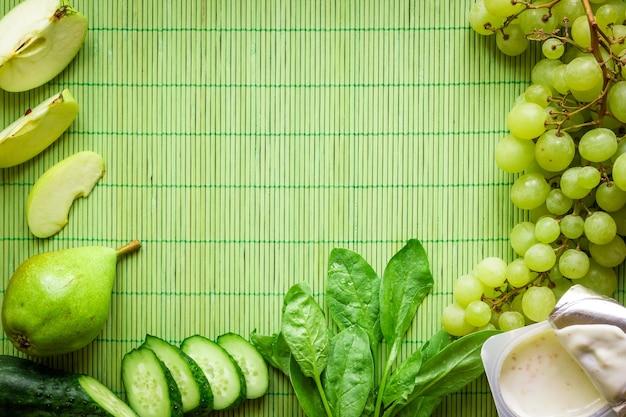 녹색 해독 스무디의 재료입니다. 녹색 배경에 시금치, 포도, 요구르트, 오이, 사과. 텍스트를 위한 장소가 있는 평평한 위치. 완전 채식 및 건강 식품 개념