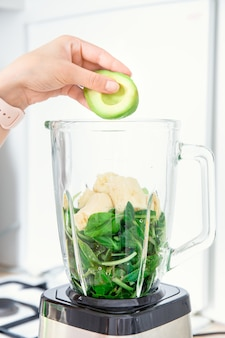 Ингредиенты для зеленых смузи для детоксикации в блендере шпинат, банан и авокадо, вид сбоку, рука наполняет блендер или миксер полезными ингредиентами авокадо и шпинат