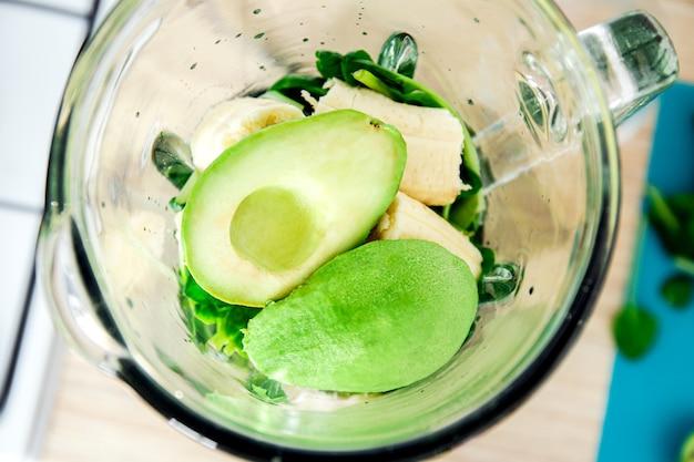 믹서기에 녹색 해독 스무디를 위한 재료입니다. 시금치, 바나나, 아보카도. 측면보기