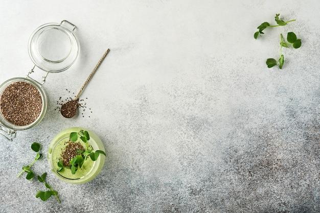 Ингредиенты для зеленого смузи, свежих органических микрозелени из шпината и гороха, банана, киви, яблока и семян чиа на светло-сером бетонном фоне. ингредиенты для здорового питания. вид сверху, копировать пространство