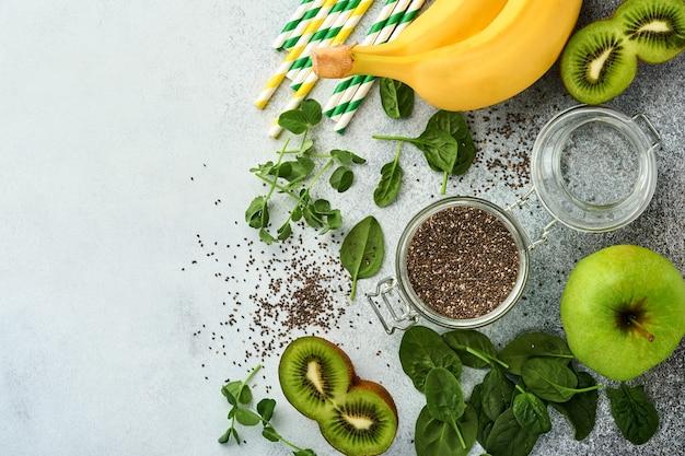 Ингредиенты для зеленого смузи, свежих органических микрозелени из шпината и гороха, банана, киви, яблока и семян чиа на светло-сером бетонном фоне. ингредиенты для здорового питания. вид сверху, копия пространства.
