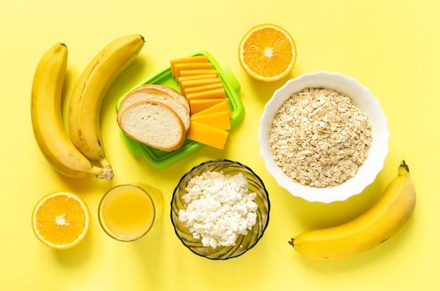 건강한 아침 식사를위한 재료. 노란색 표면, 상위 뷰에 오트밀, 유제품 및 과일.