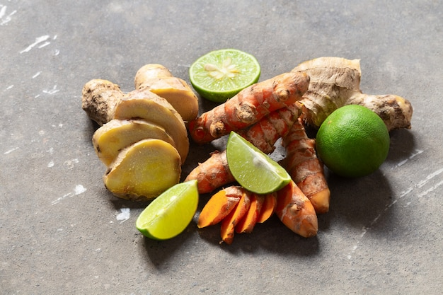 Ингредиенты для здорового напитка из куркумы и корня имбиря и лайма на серой бетонной стене с copyspace.