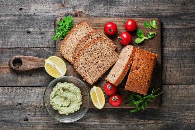 Ингредиенты для полезных бутербродов. нарезанный домашний цельнозерновой хлеб, помидоры черри, кукурузный салат, руккола и гуакамоле из авокадо.
