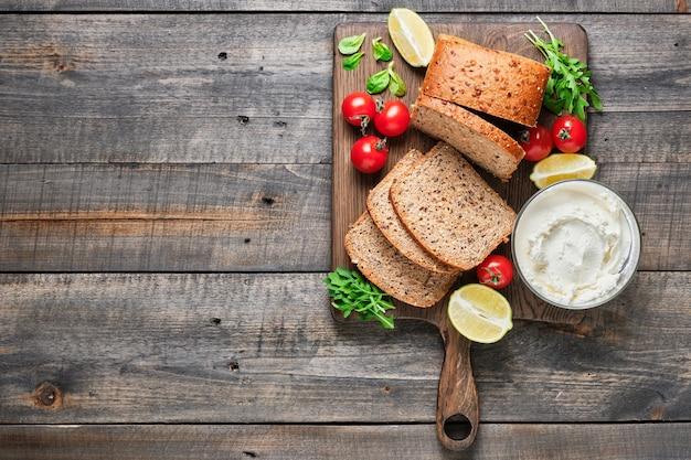 Ингредиенты для полезных бутербродов. нарезанный домашний цельнозерновой хлеб, помидоры черри, кукурузный салат, руккола и сливочный сыр.