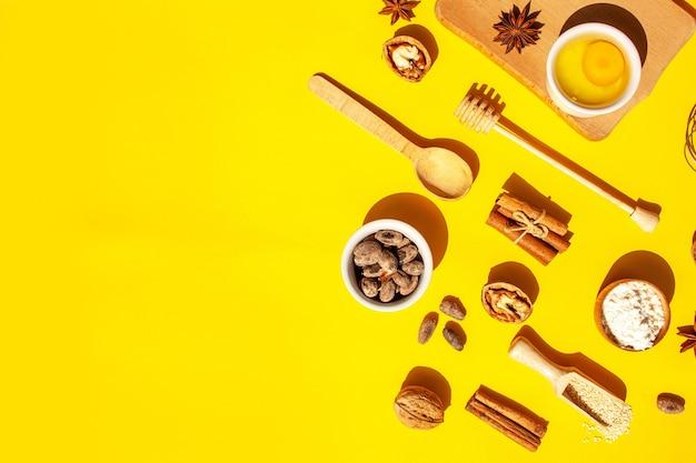 Ингредиенты для домашнего приготовления. грецкие орехи, корица, какао, мука, яйца на желтом фоне. плоский стиль