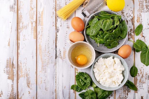 自家製タリアテッレベジタリアンエッグパスタカルボナーラの材料は、白い木製の背景の上にリコッタチーズ、卵、ほうれん草を添えて。
