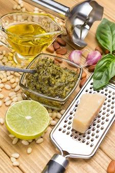 Ингредиенты для домашнего песто. сыр пармезан на терке. соус песто в стеклянной чашке. лимон и листья, базилик и масло. чеснок и кедровые орехи. измельчитель металла. вид сверху. светлый деревянный фон.
