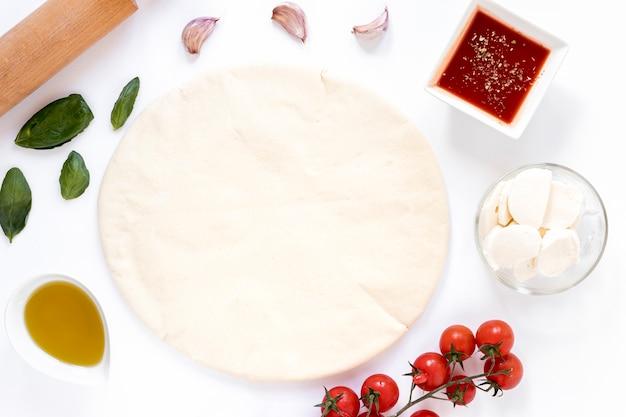 自家製ピザの白い背景で隔離のための原料
