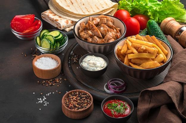 Ингредиенты для домашней шаурмы, буррито, гироскопов на коричневой стене. жареное мясо, картофель фри, овощи и лаваш. обед.