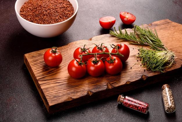 インド料理の材料は黒い表面にあります。料理の構成には玄米、ハーブ、スパイスが含まれます。