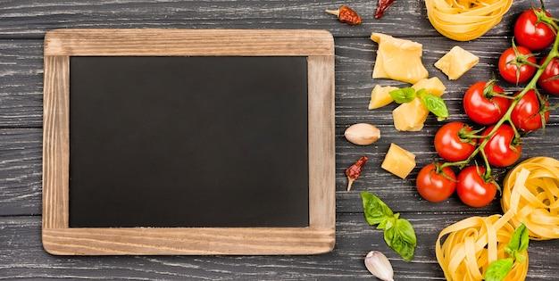 そばに黒板があるイタリア料理の食材