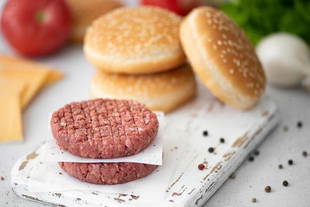 ハンバーガーを作るための材料-ホワイトボード上の肉カツ、パン、チーズ、野菜